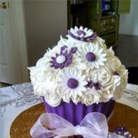 A stunning cupcake with bouquet of flowers on top.
